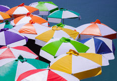 Colorful umbrellas. Open on sunny day by side of lake Royalty Free Stock Image