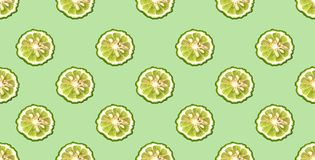 Colorful pattern of fresh bergamot slices on green background. From top view.  stock photography