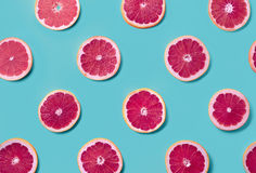 Colorful pattern of grapefruit slices. Colorful fruit pattern of fresh grapefruit slices on blue background. From top view royalty free stock photos