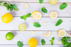Colorful pattern of mint, lime, lemon,ginger slices. . Limes and Lemons sliced and whole with leaves. On white wooden background. stock photos