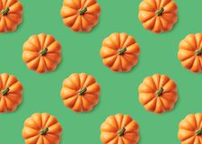 Colorful pattern of orange pumpkins on green background royalty free stock photo