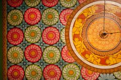 Colorful patterns of the old paintings, flowers and decor on wooden ceiling of Buddha ancient temple. Royalty Free Stock Photos