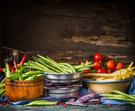 Colorful pea and bean pods in bowls on rustic kitchen table at wooden background, top view Royalty Free Stock Photography