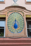 Colorful peacock sculpture adorns a historic building. Royalty Free Stock Photography