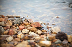 Colorful pebble, clear water with gravel at side of the lake, imafe for background. Wallpaper, copy space Royalty Free Stock Image
