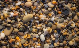Colorful pebbles on beach. Pebbles closeup background. Small round stones in sunlight. Minerals concept. Sea shore background. Pebbles wallpaper royalty free stock photography