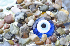 Colorful pebbles on the beach with turkish evil eye glass bead. Background with color stones on the sea and amulet. Sea shore bright stones, pebble, gravel Royalty Free Stock Images