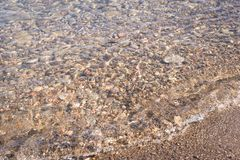 Colorful pebbles on beach in water stock photography