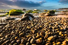Nature Seascape with Colorful Pebbles Glittering in The Morning Sunlight at A Rocky Beach royalty free stock photos