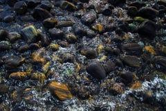Colorful pebbles touching wave at beautiful rock island, called Koh Hin Ngam, near Lipe island, Thailand Royalty Free Stock Photos