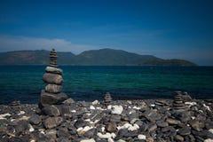 Colorful pebbles touching wave at beautiful rock island, called Koh Hin Ngam, near Lipe island, Thailand Stock Photo