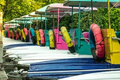 Colorful pedal boats anchor at pier in park. stock image