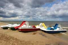 Colorful pedalos on the beach on a cloudy day stock image