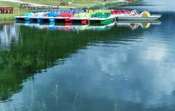Colorful pedalos on a mountain lake with reflections. Copy space stock photo