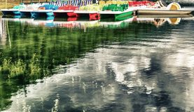 Colorful pedalos on a mountain lake with reflections. Copy space royalty free stock image