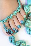 Colorful pedicure with design . Colorful pedicure with design of turquoise stones close up on woman legs royalty free stock photos