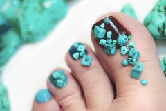 Colorful pedicure with design . Colorful pedicure with design of turquoise stones close up on woman legs royalty free stock photography
