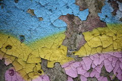 Colorful peeling paint on a concrete surface. Close-up view of old peeling paint and graffiti on a weathered concrete surface stock photo