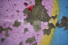 Colorful peeling paint on a concrete surface. Close-up view of old peeling paint and graffiti on a weathered concrete surface stock photos