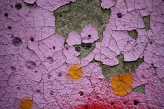 Colorful peeling paint on a concrete surface. Close-up view of old peeling paint and graffiti on a weathered concrete surface stock images