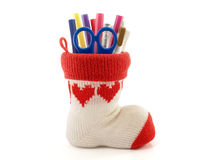 Colorful pen and blue scissors in pen holder made of knitted yarn sock with red heart pattern isolated on white background. Pen holder made of knitted yarn sock Royalty Free Stock Photos