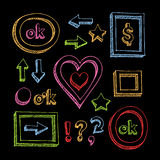Colorful pen hand drawn elements. Colorful chalk hand drawn arrows, frame, cute hearts and elements on the black background Stock Images