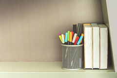 Colorful pen in metal pen pot and books on shelve Royalty Free Stock Photography