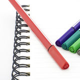 Colorful pen with notebook isolated on white Stock Images