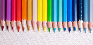 Colorful pencil crayons. On the background fabric Royalty Free Stock Image