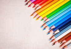 Colorful pencil crayons. On the background fabric Royalty Free Stock Images