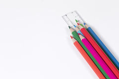 Colorful pencil crayons and ruler on white. With copy space in a back to school or education concept Royalty Free Stock Photos