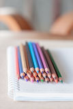 Colorful pencil crayons on spiral notebook Royalty Free Stock Photo