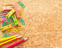Colorful pencil and paperclips on old paper background Royalty Free Stock Images