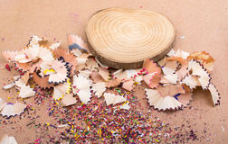 Colorful pencil shavings and  piece of wood Stock Photos