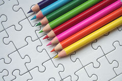 Colorful pencils. On a jigsaws background stock photography