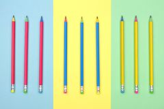 Colorful pencils against a multicolor pastel background. Colorful school pencils against a pastel blue, yellow and green paper background royalty free stock photography
