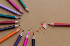 Colorful pencils arranged in half circular pattern with pencil shavings Stock Photo
