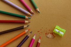 Colorful pencils arranged in half circular pattern with pencil shavings and yellow sharpener Royalty Free Stock Images