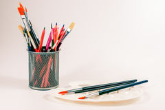 Colorful pencils and art palette with brushes in a cup Stock Images
