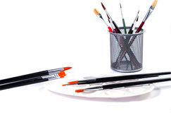 Colorful pencils and art palette with brushes in a cup Royalty Free Stock Images