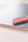 Colorful pencils on black notebook Royalty Free Stock Photo
