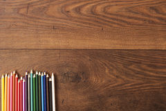 Colorful pencils on the brown wooden table background. Frame of colored pencils over wood with free space for text Royalty Free Stock Image