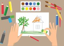 Cute children drawing with paints and crayons. Colorful pencils and brushes lying around sketchbook with kids crayon drawing of home, cloud, tree and sun Royalty Free Stock Photos