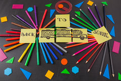 Colorful pencils in circles, titles Back to school and school bus drawn on the   pieces of paper on the chalkboard Stock Photos