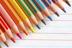 Colorful pencils crayons on white paper Royalty Free Stock Photos