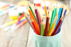Colorful pencils in cup on the grey wooden background Royalty Free Stock Images