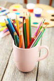 Colorful pencils in cup on the grey wooden background Stock Photography