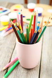 Colorful pencils in cup on the grey wooden background Royalty Free Stock Photography