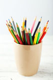 Colorful pencils in cup on the white wooden background Stock Image
