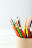 Colorful pencils in cup on the white wooden background Stock Photos